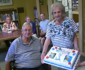 HAL TO CELEBRATE-- David MacMillan and Theodora Rose, two of the late Hal Smith's first cousins, display a custom cake as others look on during the party marking Hal's 100th birthday. Photo by John D. Michaud III.